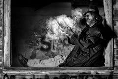 Mann im Fenster des alten Hauses Stockfotos
