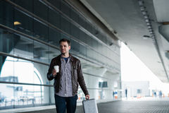 Mann im Flughafen, der eine Tasche hält und mit Tasse Kaffee geht Stockfotos