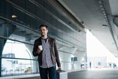 Mann im Flughafen, der eine Tasche hält und mit Tasse Kaffee geht Stockfoto