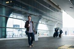 Mann im Flughafen, der eine Tasche hält und mit Tasse Kaffee geht Lizenzfreie Stockfotos