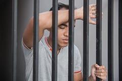 Mann im Gefängnis hinter Gittern Lizenzfreies Stockfoto