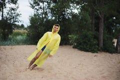 Mann im gelben Regenmantel durchgebrannt weg durch den Wind fällt lizenzfreies stockbild