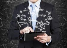 Mann im Gesellschaftsanzug hält eine Tablette mit Matheformelprojektion auf der Luft lizenzfreies stockbild