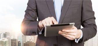 Mann im Gesellschaftsanzug sucht nach etwas Daten in der Tablette Panorama von New York City auf dem Hintergrund Lizenzfreie Stockfotos
