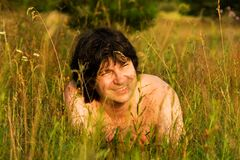 Mann im Gras am sonnigen Tag Stockbild