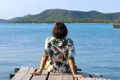 Mann im Hawaiihemd sitzt am Ende der Holzbrücke stockfotografie