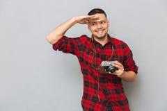 Mann im Hemd, das Retro- Kamera hält und Kamera betrachtet Lizenzfreie Stockfotos