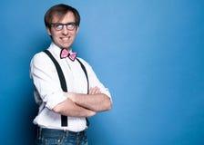 Mann im Hemd, in Hosenträger, in der rosa Fliege und in der Glasstellung, lächelnd mit den gekreuzten Armen stockfotografie