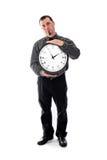 Mann im Hemd und Bindung, die große Uhr hält Stockfotografie