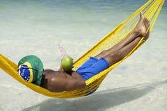 Mann im Hängematten-brasilianischen Strand mit Kokosnuss Stockfoto