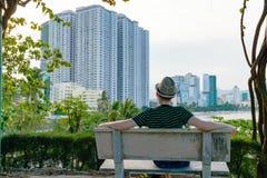 Mann im Hut betrachtet Strand mit Wolkenkratzern lizenzfreie stockfotos
