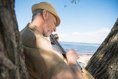Mann im Hut, der auf Baum sich lehnt und Gitarre am Flussufer spielt Lizenzfreie Stockfotos