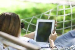 Mann im Hut in einer Hängematte mit Tablet-Computer an einem Sommertag Lizenzfreies Stockbild