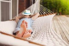 Mann im Hut in einer Hängematte an einem Sommertag Lizenzfreie Stockfotografie