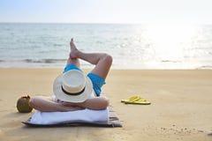 Mann im Hut mit Kokosnusscocktail auf dem Strand lizenzfreies stockfoto