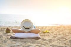 Mann im Hut mit Kokosnusscocktail auf dem Strand stockbild