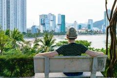 Mann im Hut sitzt auf der Bank, die Strand mit Wolkenkratzern betrachtet stockbilder