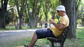Mann im Hut und in der Sonnenbrille benutzt Smartphone im Park auf der Bank Mann unter Verwendung des Smartphone bei der Entspann stock footage