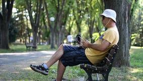 Mann im Hut und in der Sonnenbrille hört Musik, die sich auf Bank im Park hinsetzt Mann hört Musik mit Telefon bei der Entspannun stock video footage
