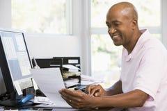 Mann im Innenministerium unter Verwendung des Computers und des Lächelns Stockbild