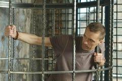 Mann im Käfig mit den Händen Stockfotos