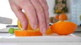 Mann im Küchenschnitt für orange Frucht des Salats in den neuen süßen und gewürzten Scheiben stock footage