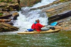Mann im Kajak an einem Wasserfall Lizenzfreie Stockbilder