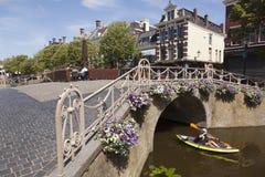 Mann im Kanu führt bunte Blumen auf Brücke in der Mitte von altem Stockbild
