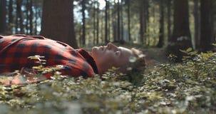 Mann im karierten Hemd, das bei geschlossenen Augen in einem Wald liegt Lizenzfreies Stockfoto