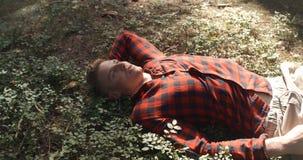 Mann im karierten Hemd, das bei geschlossenen Augen in einem Wald liegt Lizenzfreies Stockbild