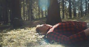 Mann im karierten Hemd, das bei geschlossenen Augen in einem Wald liegt stock video