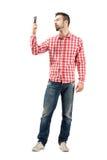 Mann im karierten Hemd sein intelligentes Telefon überprüfend Lizenzfreies Stockfoto