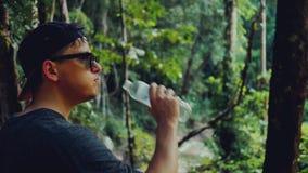 Mann im Kauf des Trinkwassers in einem heißen tropischen Wald stock video