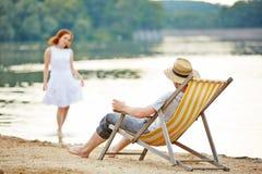 Mann im Klappstuhl, der zur Frau im Wasser schaut Stockfotos