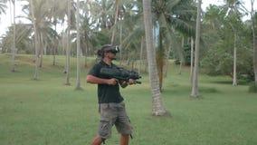 Mann im Kopfhörer der virtuellen Realität mit Waffe im Dschungel, der in Zeitlupe läuft stock video footage