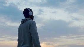 Mann im Kopfhörer hörend Musik, Gedächtnisse und Gedanken genießend, magische Stunde stock video