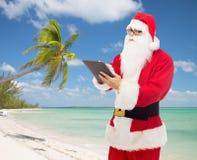 Mann im Kostüm von Weihnachtsmann mit Tabletten-PC Lizenzfreie Stockbilder