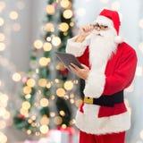 Mann im Kostüm von Weihnachtsmann mit Tabletten-PC Stockbild