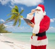 Mann im Kostüm von Weihnachtsmann mit Tabletten-PC Lizenzfreie Stockfotografie