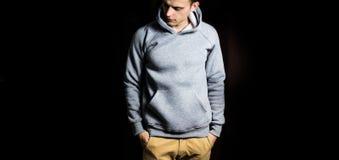 Mann im leeren grauen Hoodie, Sweatshirt auf einem schwarzen Hintergrund, Spott oben, freier Raum lizenzfreie stockfotos