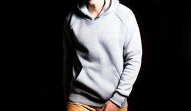 Mann im leeren grauen Hoodie, Sweatshirt auf einem schwarzen Hintergrund, Spott oben, freier Raum stockbild
