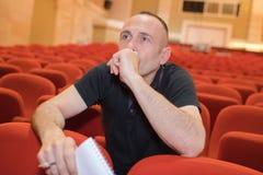 Mann im leeren Theater, das Notizbuch hält stockfotografie