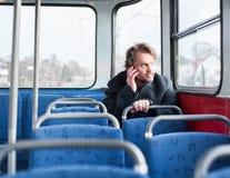 Mann im Mantel, der am Telefon spricht Stockbilder