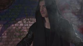Mann im Mantel mit einer Haube auf seiner Hauptstellung im Feuer Brennen des Zauberers Kamera, die sich nach unten bewegt stock footage