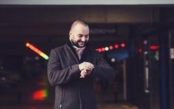 Mann im Mantel mit Uhr stockfotografie