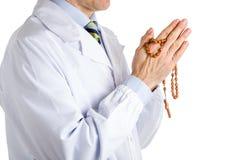 Mann im medizinischen weißen Mantel, der hölzerne Rosenkranzperlen hält Stockfotografie