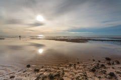 Mann im Meer und im Sonnenaufgang Lizenzfreies Stockbild