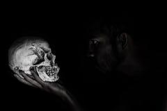 Mann im menschlichen Schädel der Schattenstarren, das in der Hand halten Lizenzfreies Stockfoto