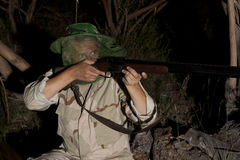 Mann im Moskitonetz bereit, mit Jagdgewehr zu jagen Lizenzfreies Stockbild