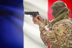 Mann im moslemischen keffiyeh mit Gewehr in der Hand und Staatsflagge auf Hintergrund - Frankreich Stockbilder